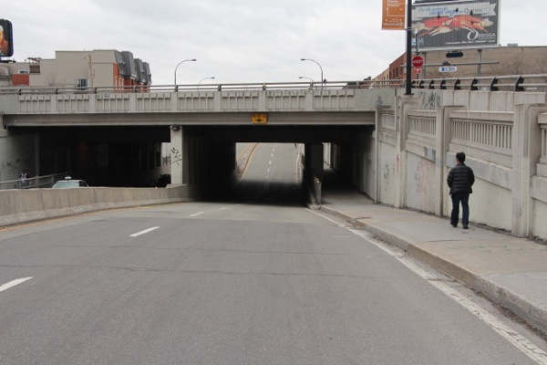 The right lane on Saint-Denis St. narrows as it approaches the overpass.